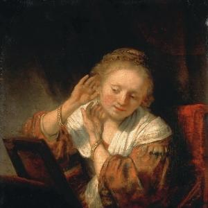 Рембрандт Харменс ван Рейн - Молодая женщина, примеряющая серьги
